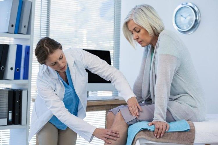 female-doctor-examining-female-patients-leg